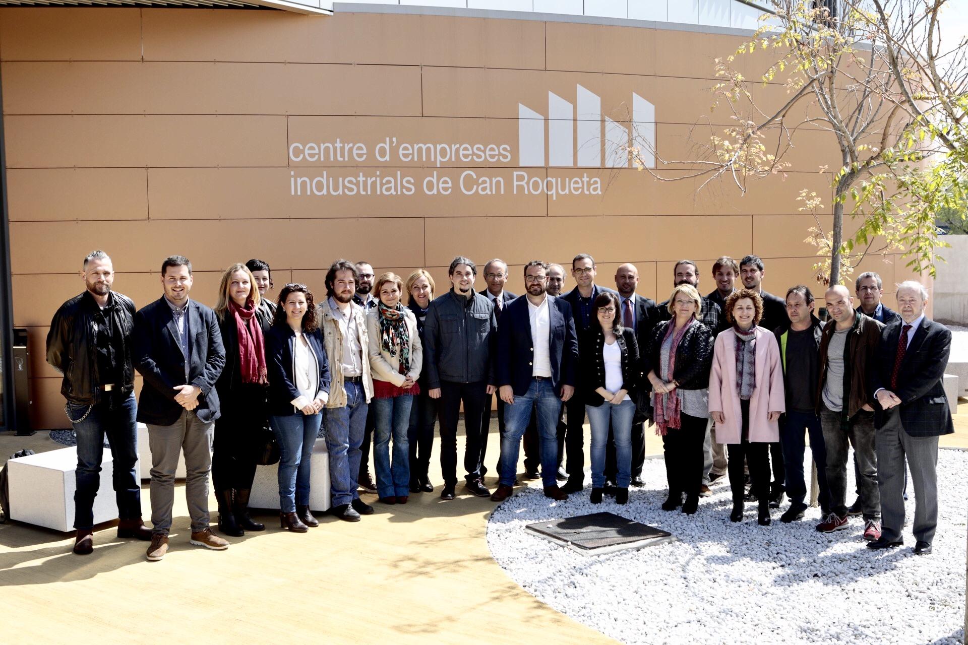 Grup de persones davant del centre d'empreses industrials de Can Roqueta